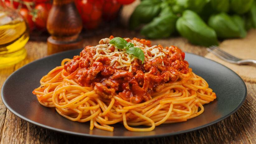 Spaghetti bolognese na czarnym talerzu na drewnianym stole