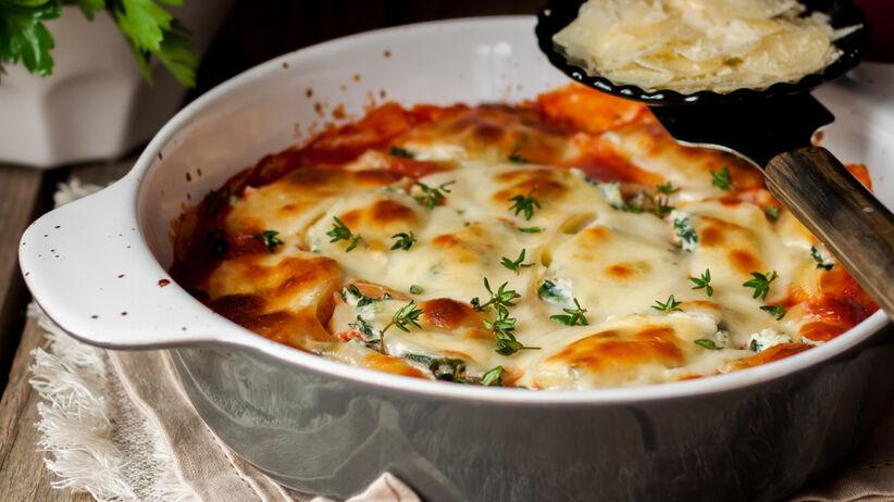 Zapiekanka ziemniaczana z mięsem mielonym posypana serem w naczyniu żaroodpornym