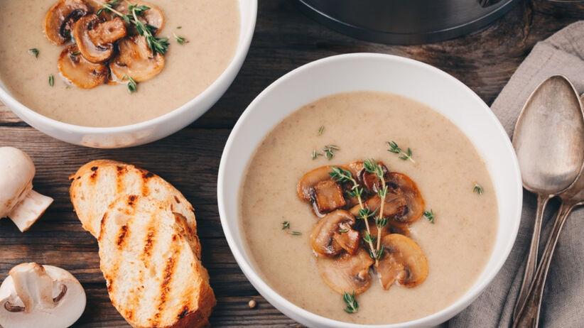 Zupa krem z borowików w miseczce, z borowikami na wierzchu i grzankami obok