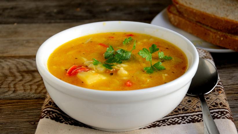 Zupa ziemniaczana czyli klasyczna kartoflanka w białej misce z chlebem stoi na stole