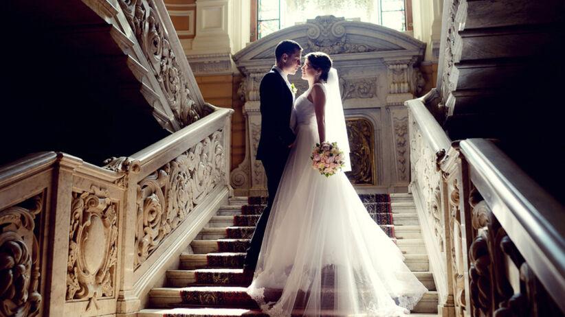 Panna młoda w sukni i pan młody w garniturze na schodach z czerwonym dywanem w kościele