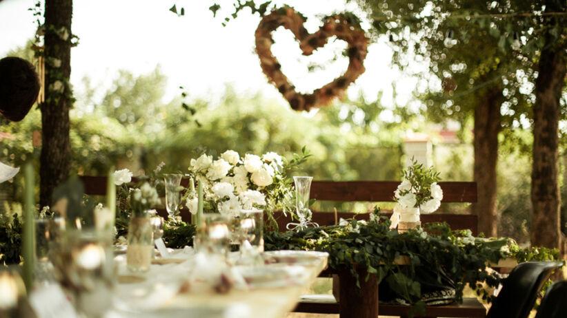 Pięknie udekorowana sala weselna z sercem kwiatów za parą młodą