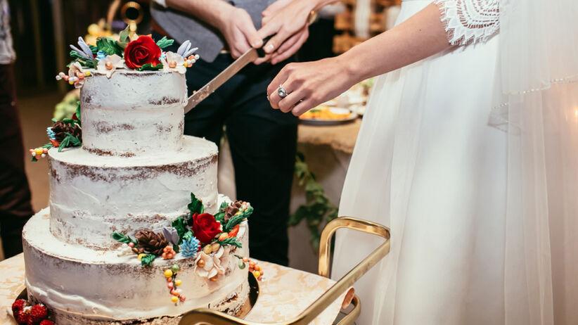 Para młoda kroi tort weselny w stylu rustykalnym na weselu