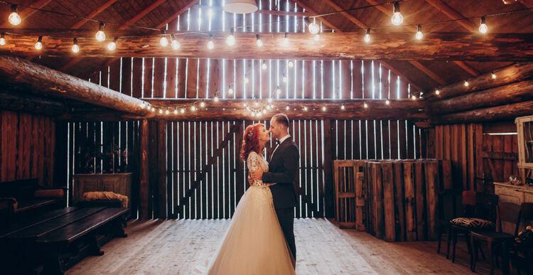 Para młoda w pięknej, rustykalnej sali weselnej
