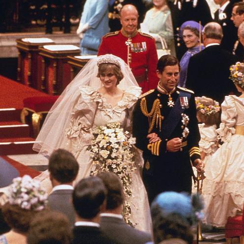 Księżna Diana i książę Karol w strojach ślubnych idą po czerwonym dywanie między gośćmi w kościele podczas swojego ślubu