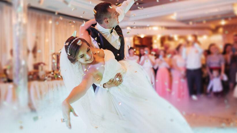 Panna młoda w białej sukni i pan młody w garniturze tańczą pierwszy taniec
