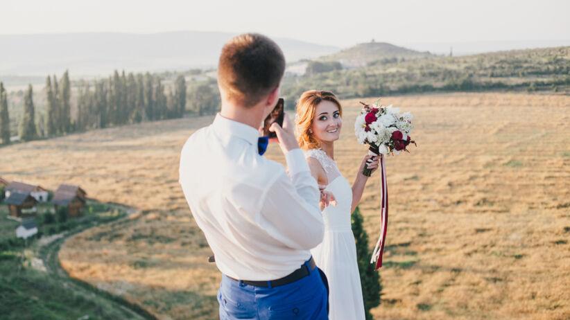 Pan młody robi zdjęcie pani młodej na plenerze ślubnym