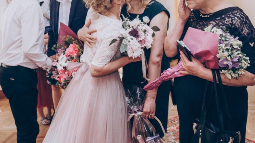 Para młoda wręcza prezenty dla rodziców podczas wesela