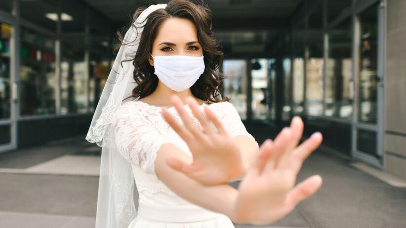 Panna młoda w suknie ślubnej, welonie i masce ochronnej
