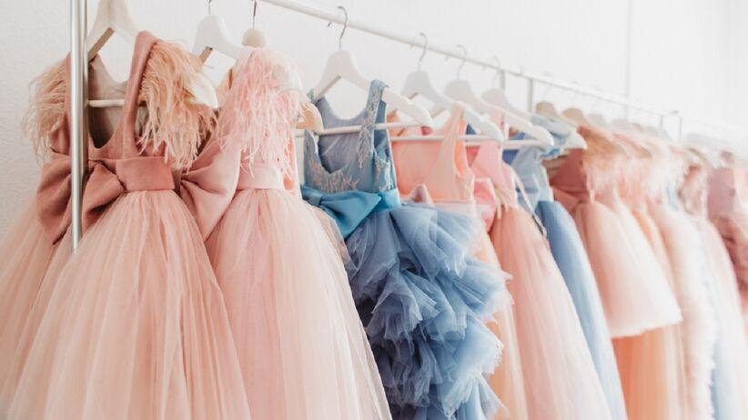 Na wieszaku wiszą sukienki weselne.