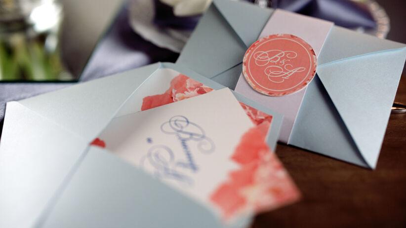 Pastelowe zaproszenia ślubne z ładną czcionką leżą na stole