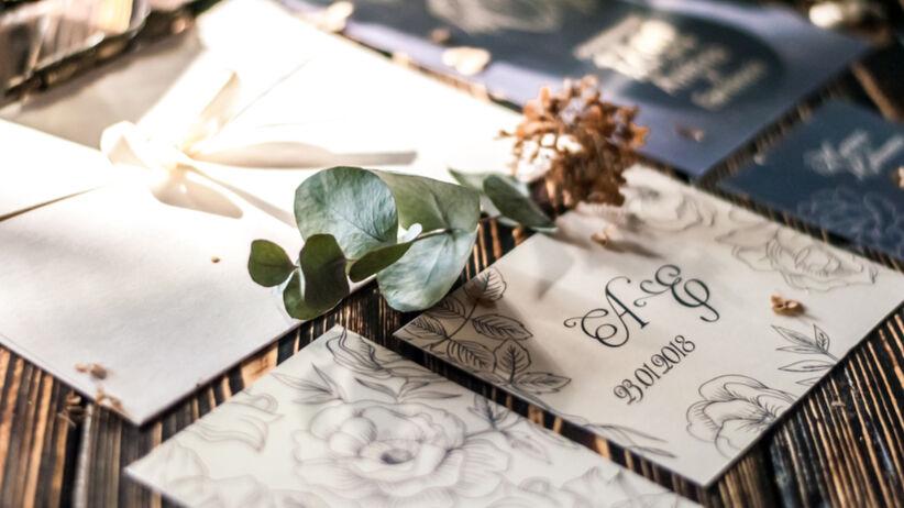 Zaproszenia ślubne leżą na drewnianym stole, a obok jest wysuszony kwiat