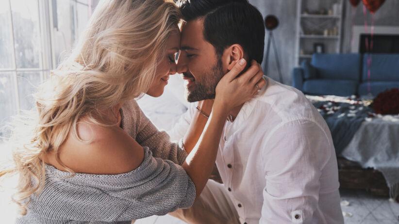 Para siedzi na łóżku i przytula się. Dziewczyna w szarym swetrze, a chłopak w białej koszuli.
