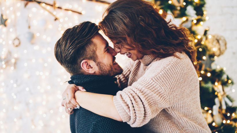 Para przytula się na tle świątecznych dekoracji