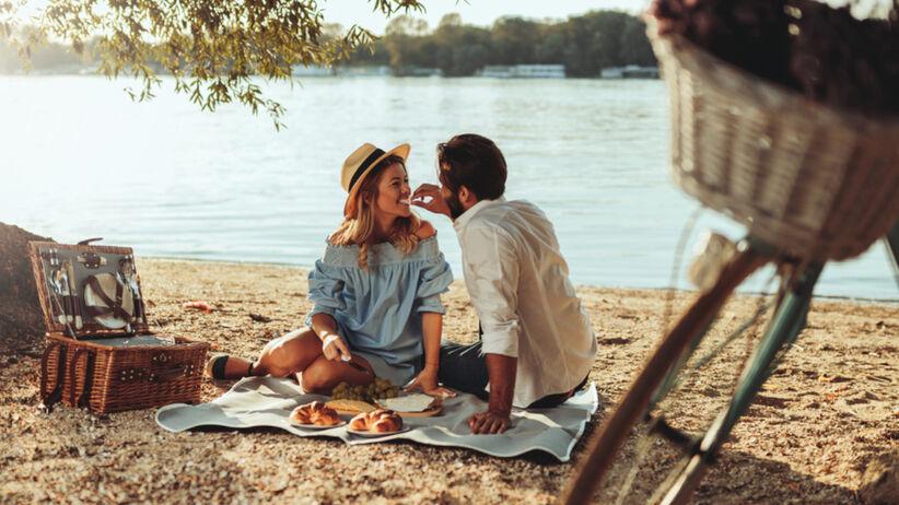 Zakochana para na kocyku na plaży nad rzeką je piknik