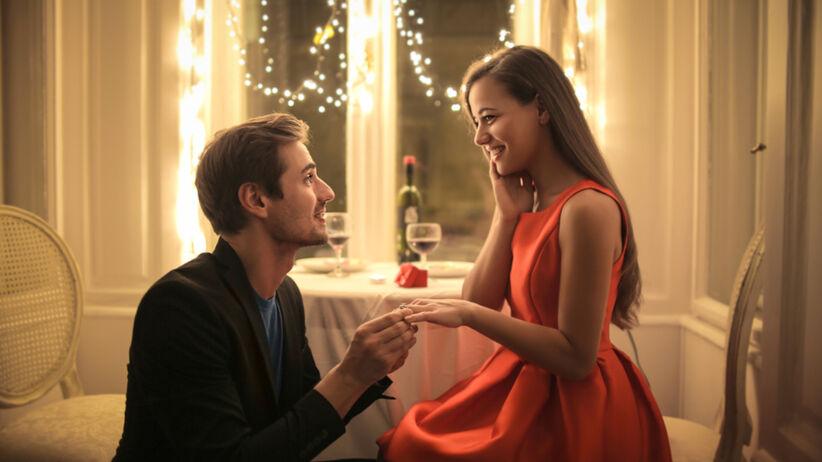 Mężczyzna w garniturze oświadcza się kobiecie w czerwonej sukience, która jest jego zdaniem idealną kandydatką na żonę