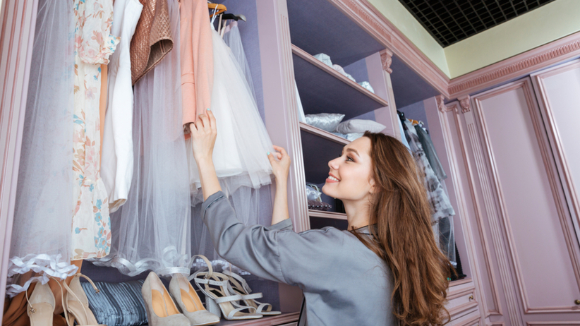 Młoda uśmiechnięta kobieta przebiera ubrania w garderobie