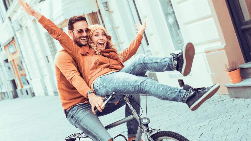Idealny mężczyzna i kobieta na rowerze w mieście doskonale się bawi