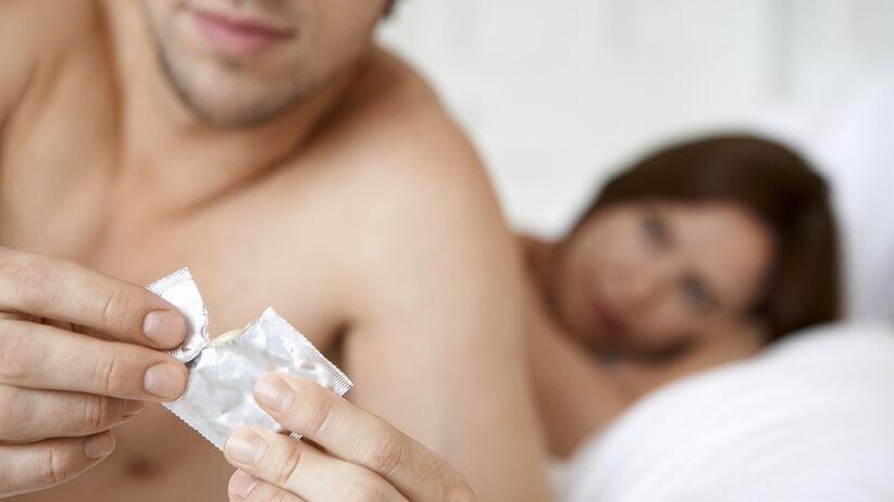 mężczyzna rozpakowujący prezerwatywę chwilę przed seksem