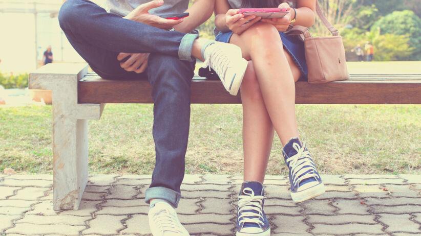 Młoda para siedzi na ławce z telefonami w rękach