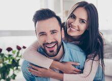 Na zdjęciu pozuje uśmiechnięte małżeństwo. W tle widać czerwone róże.