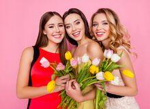 Na różowym tle pozują trzy młode kobiety. W rękach trzymają tulipany.