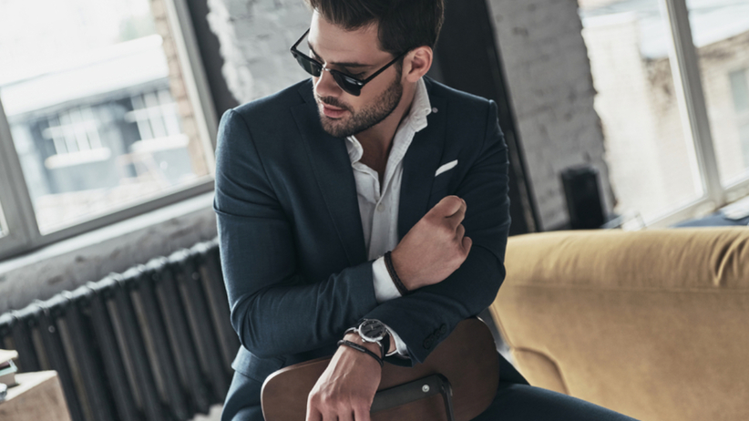 Przystojny mężczyzna w garniturze i ciemnych okularach siedzi na krześle