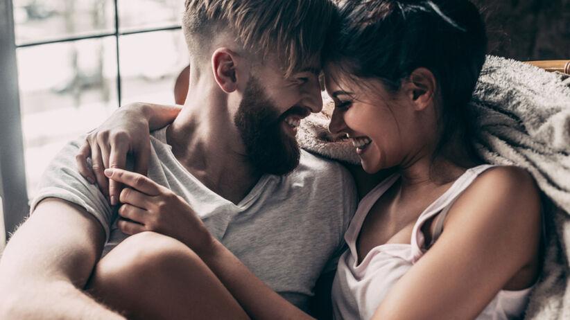 Szczęśliwa para w objęciach śmieje się beztrosko w swoim mieszkaniu