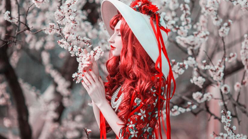 Kobieta z czerwonymi włosami i w kapeluszu na tle kwitnącej wiśni