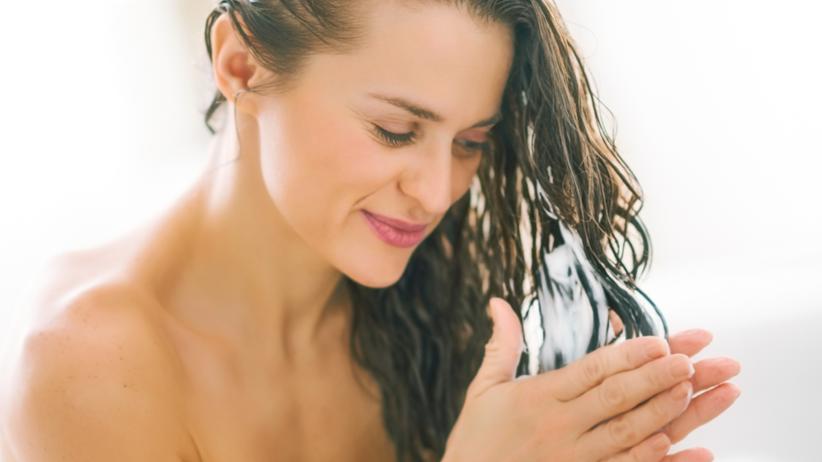 Kobieta wciera odżywkę we włosy