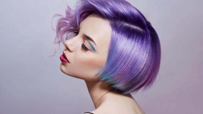 Piękna dziewczyna w krótkich fioletowych włosach na jednolitym tle