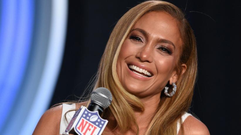 Jennifer Lopez uśmiechnięta w białym kostiumie na konferencji prasowej przed Super Bowl
