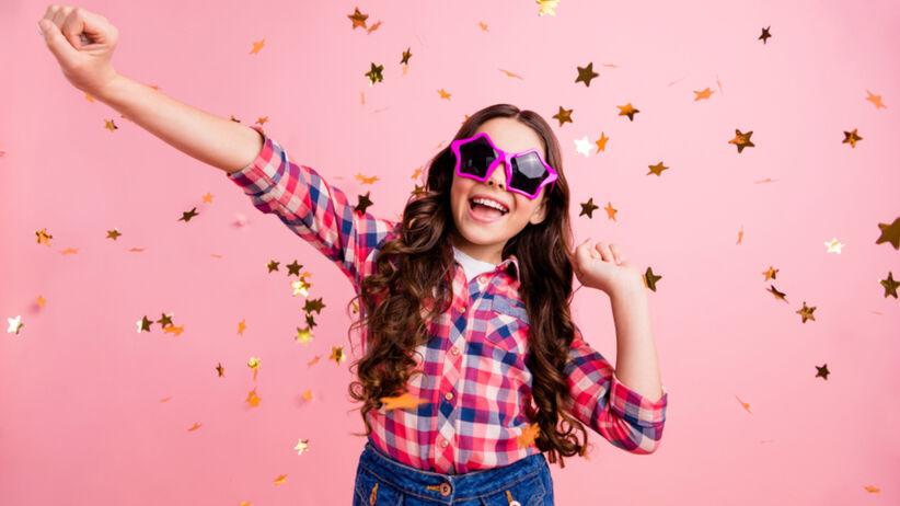 Dziewczynka w kraciastej koszuli i okularach gwiazdkach z lokami na różowym tle