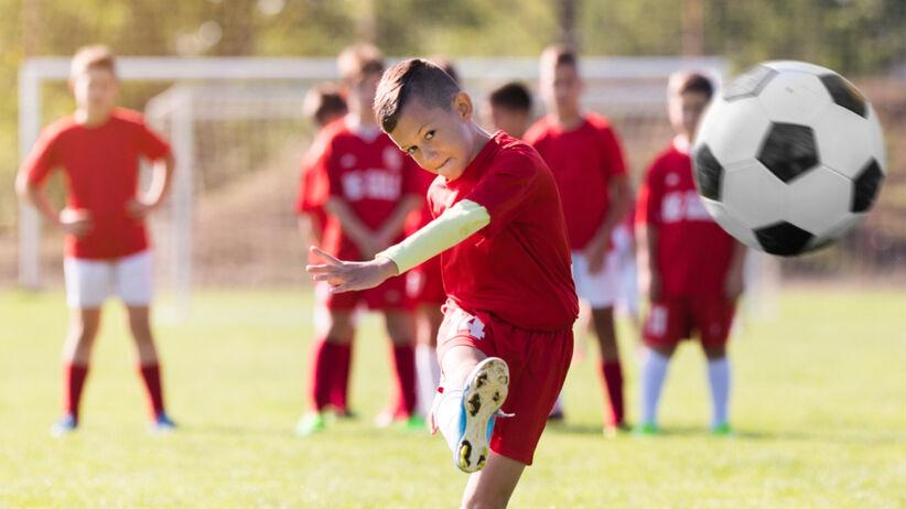Chłopiec w krótkiej fryzurze i czerwonym stroju piłkarskim kopie piłkę na boisku