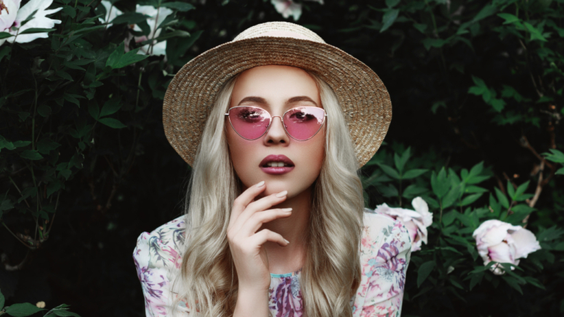 Dziewczyna w okularach i słomkowym kapeluszu o włosach w kolorze popielatego blondu wiosną przy kwiatach