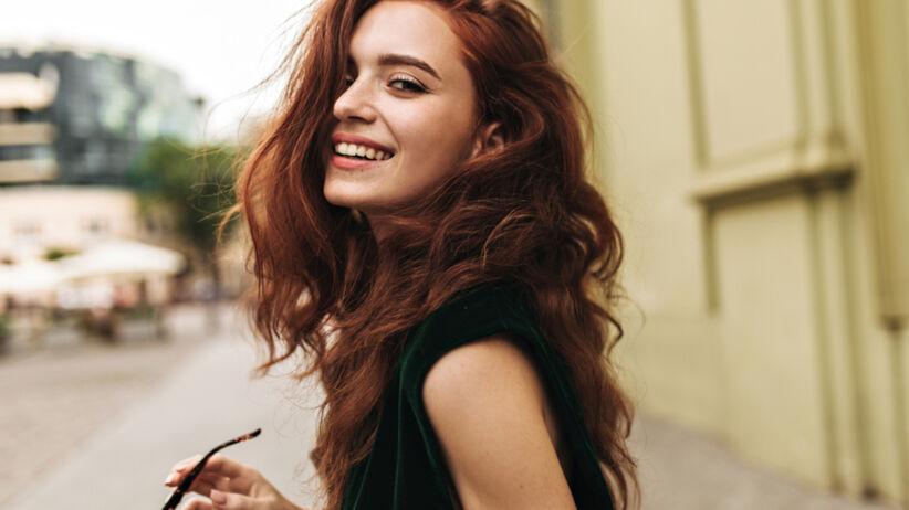 Kobieta z rudymi, długimi lokami i w zielonej bluzce cieszy się do zdjęcia