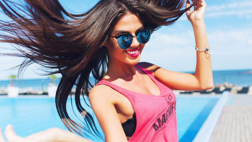 Uśmiechnięta dziewczyna w okularach prezentuje swoje piękne włosy