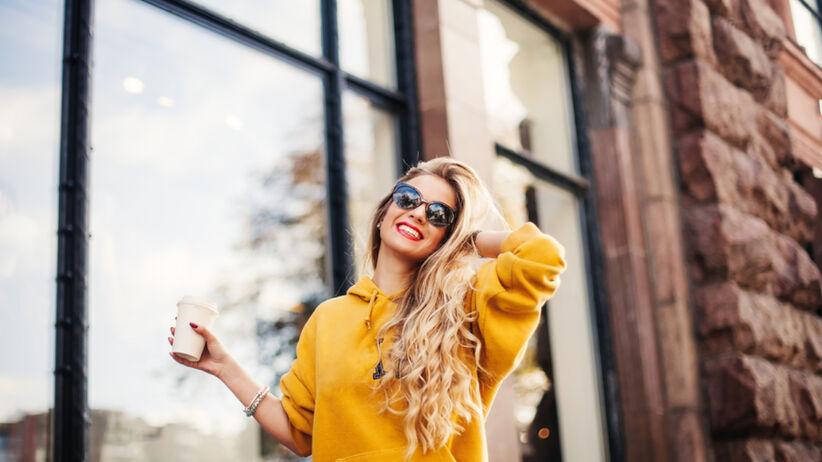 Blondynka w żółtej bluzie i z czerwonymi ustami i okularami przeciwsłonecznymi idzie po mieście z kawą uśmiechnięta