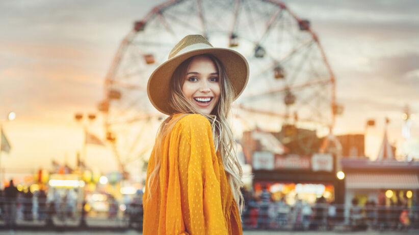 Uśmiechnięta blondynka w kapeluszu w wesołym miasteczku