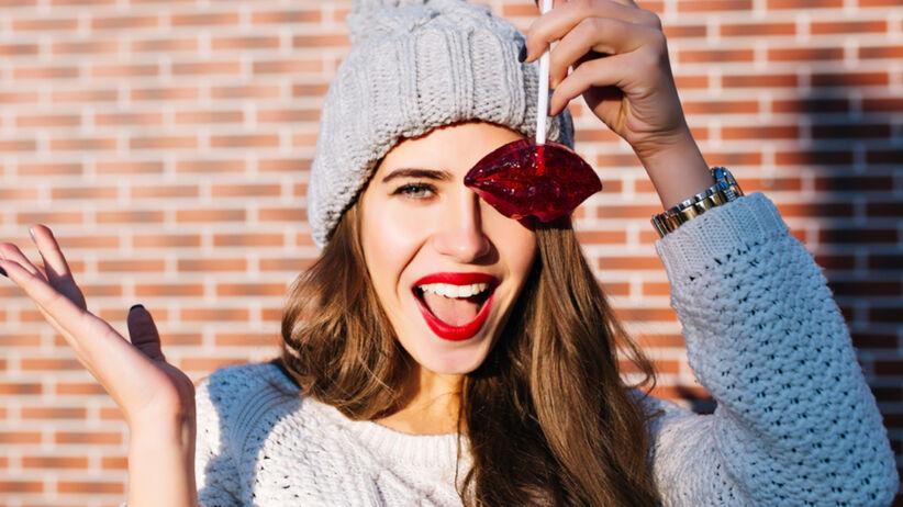 Uśmiechnięta dziewczyna z włosami w kolorze karmelu, szarą czapką, czerwonymi ustami i lizakiem przy oku