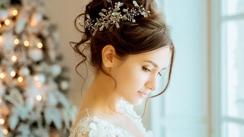 Panna młoda w białej sukni z kokiem na głowie
