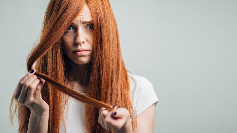 Rudowłosa kobieta, która ma zniszczone włosy i próbuje o nie zadbać