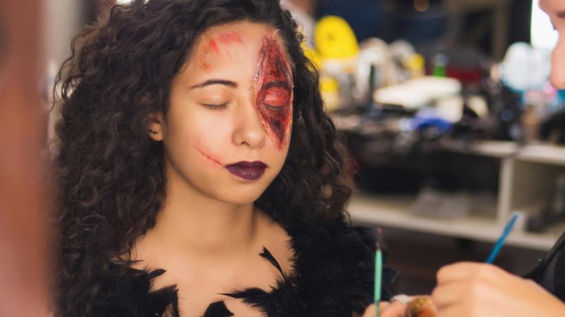 Dziewczyna jest malowana przez kosmetyczkę kosmetykami do makijażu na Halloween