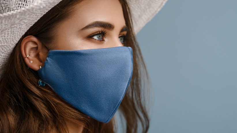 Piękna dziewczyna z mocnym makijażem w maseczce ochronnej i białym kapeluszu