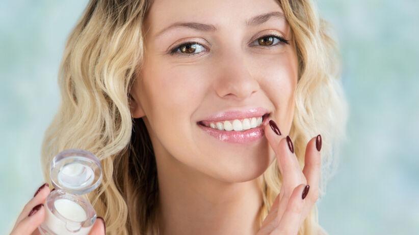 Piękna, młoda blondynka maluje usta błyszczykiem do ust