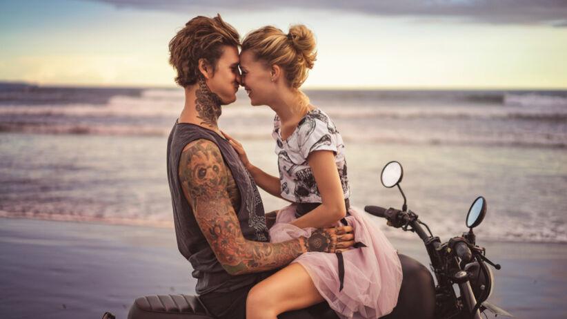 Mężczyzna z tatuażami i kobieta siedzą przytuleni na motorze