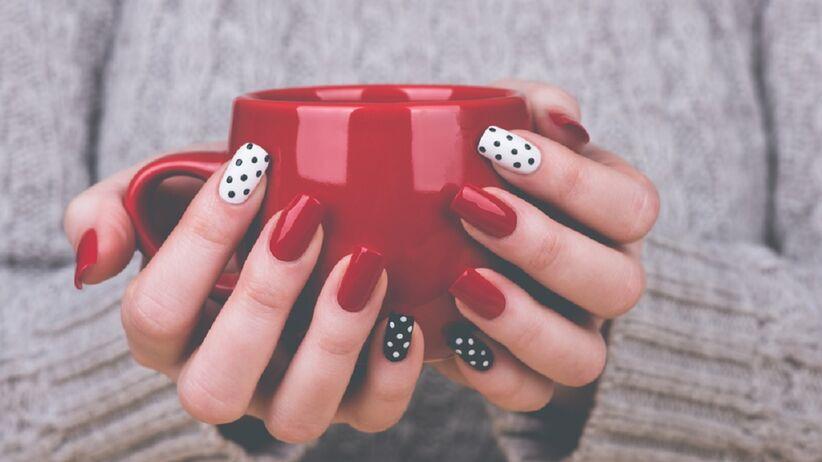 Kobieta z pomalowanymi paznokciami trzyma kubek