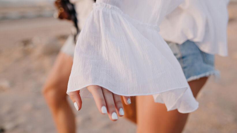 Młoda dziewczyna z białymi paznokciami, w jeansowych spodenkach i białej bluzce vintage