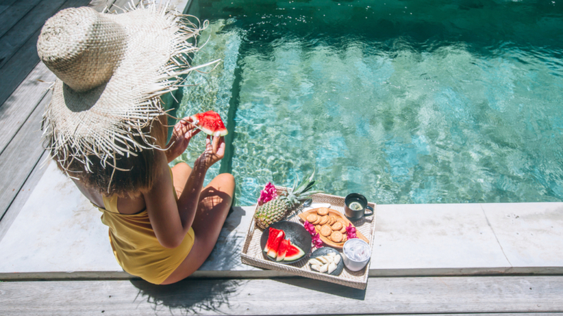 Kobieta z piękną skórą je zdrowe produkty nad basenem w upalny dzień