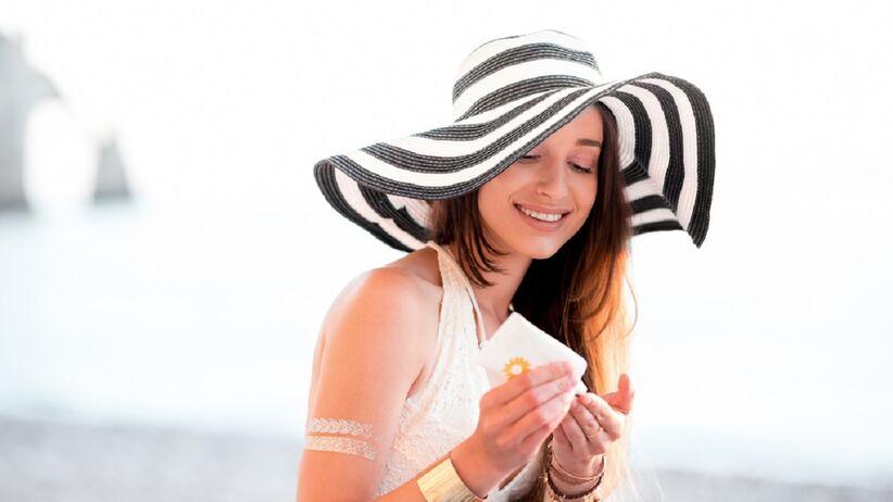 Kobieta smaruje się kremem z filtrem